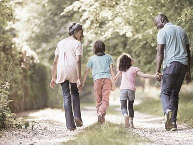 family holding hands walking outside
