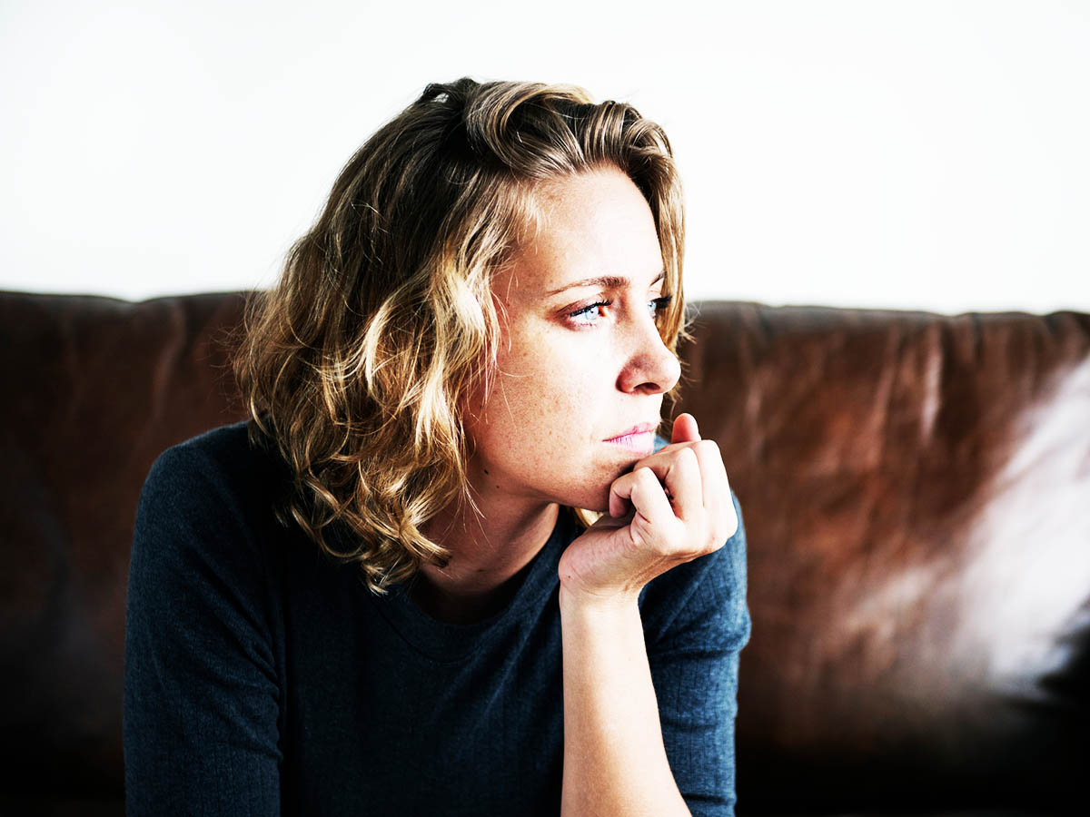 Woman looking concerned outside window