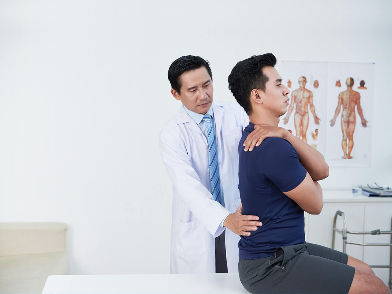 Doctor assessing a man's spine