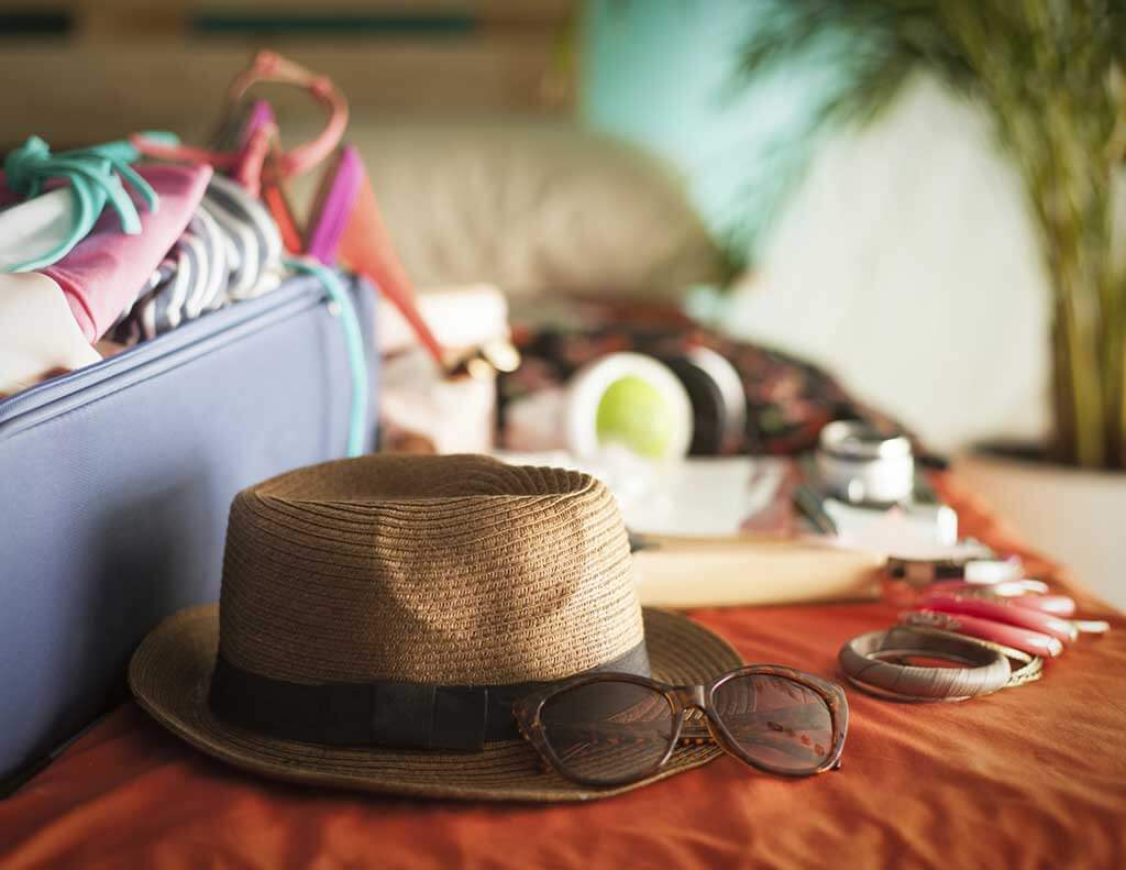 Hat and travel items on bed