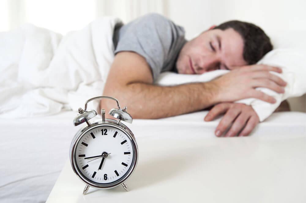 Man sleeping on bed next to alarm clock