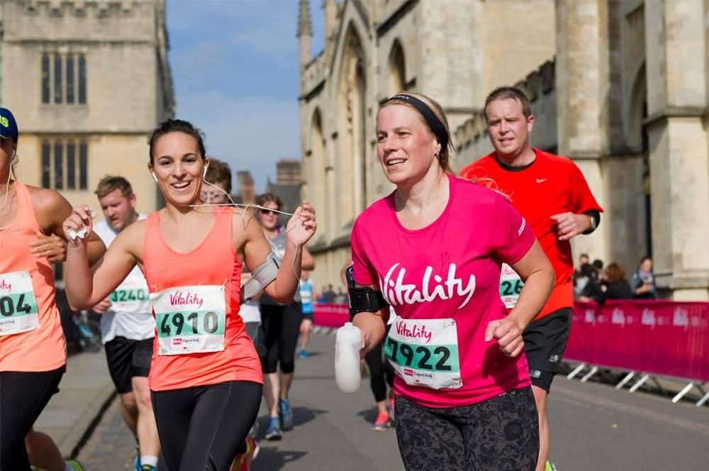 Woman wearing Vitality shirt running