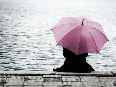 person sitting with umbrella