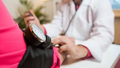 GP taking patients blood pressure