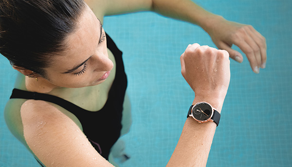 Woman swimming and looking at fitness tracker in swimming pool