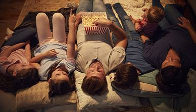 Family lying down watching a film together