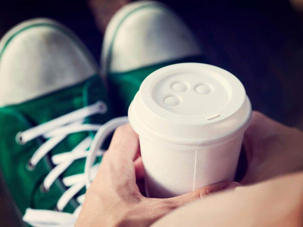Close-up of coffee and feet