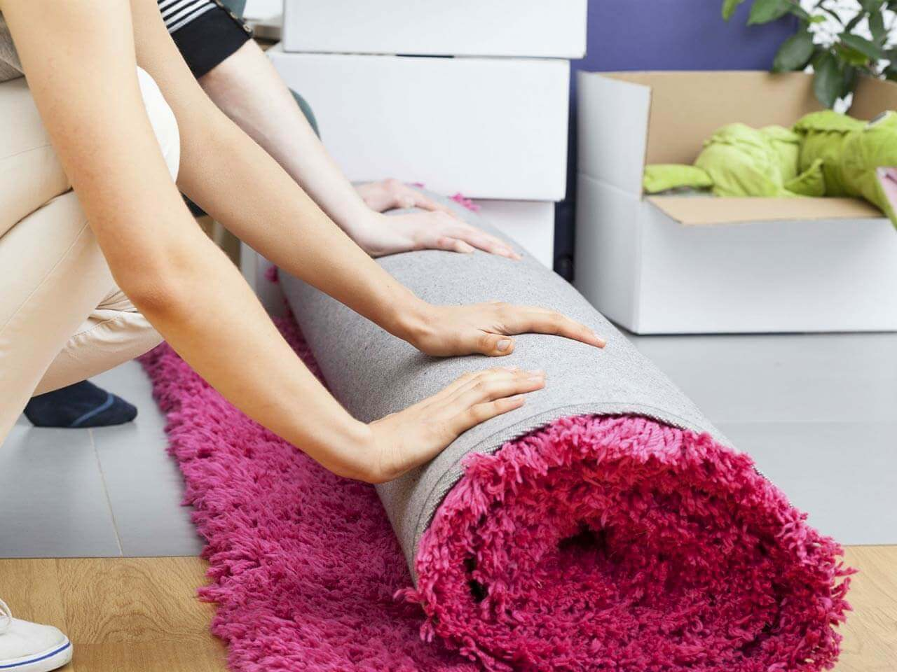 Couple unrolling carpet
