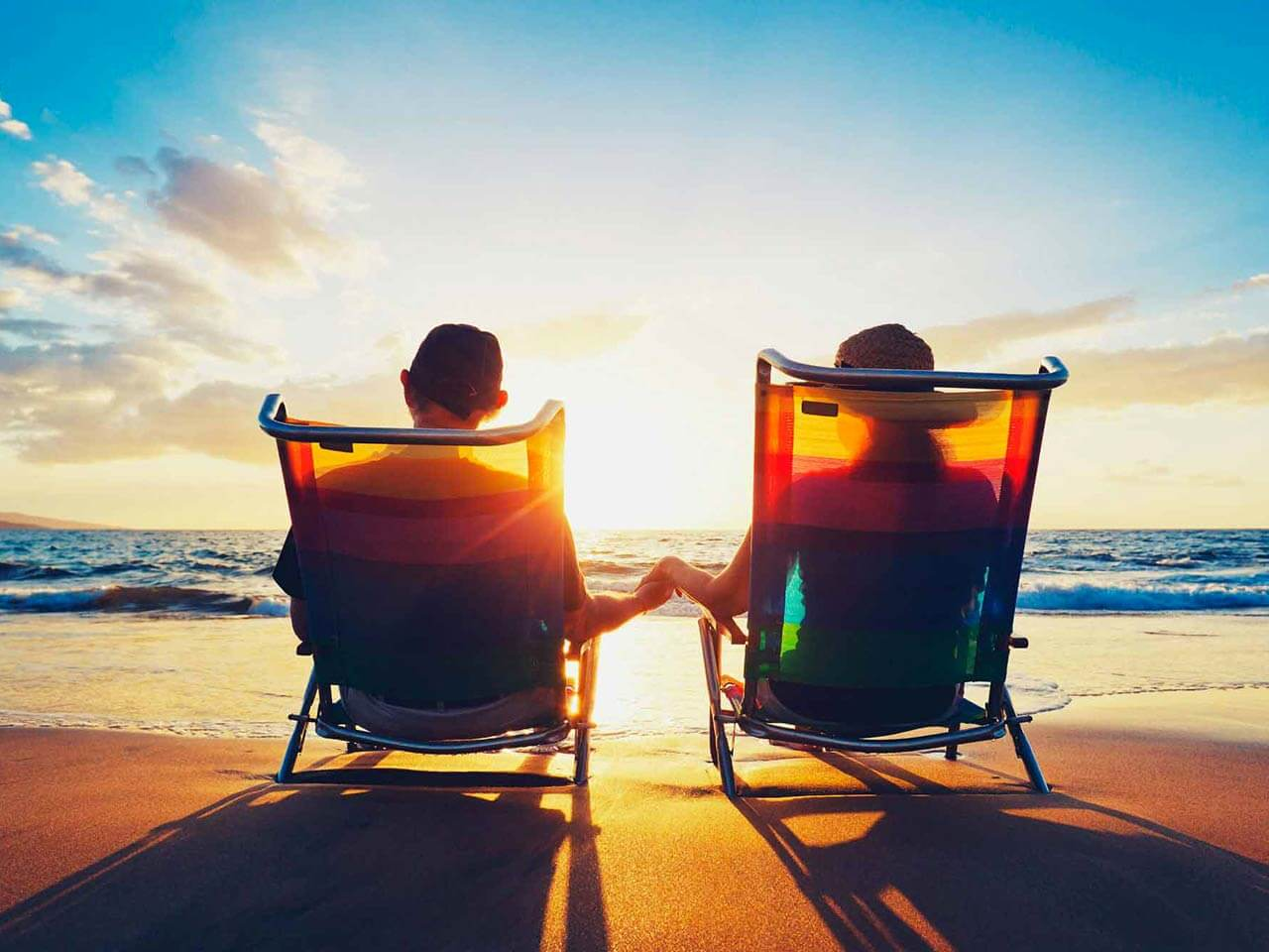 Couple sitting in deckchairs at the beach