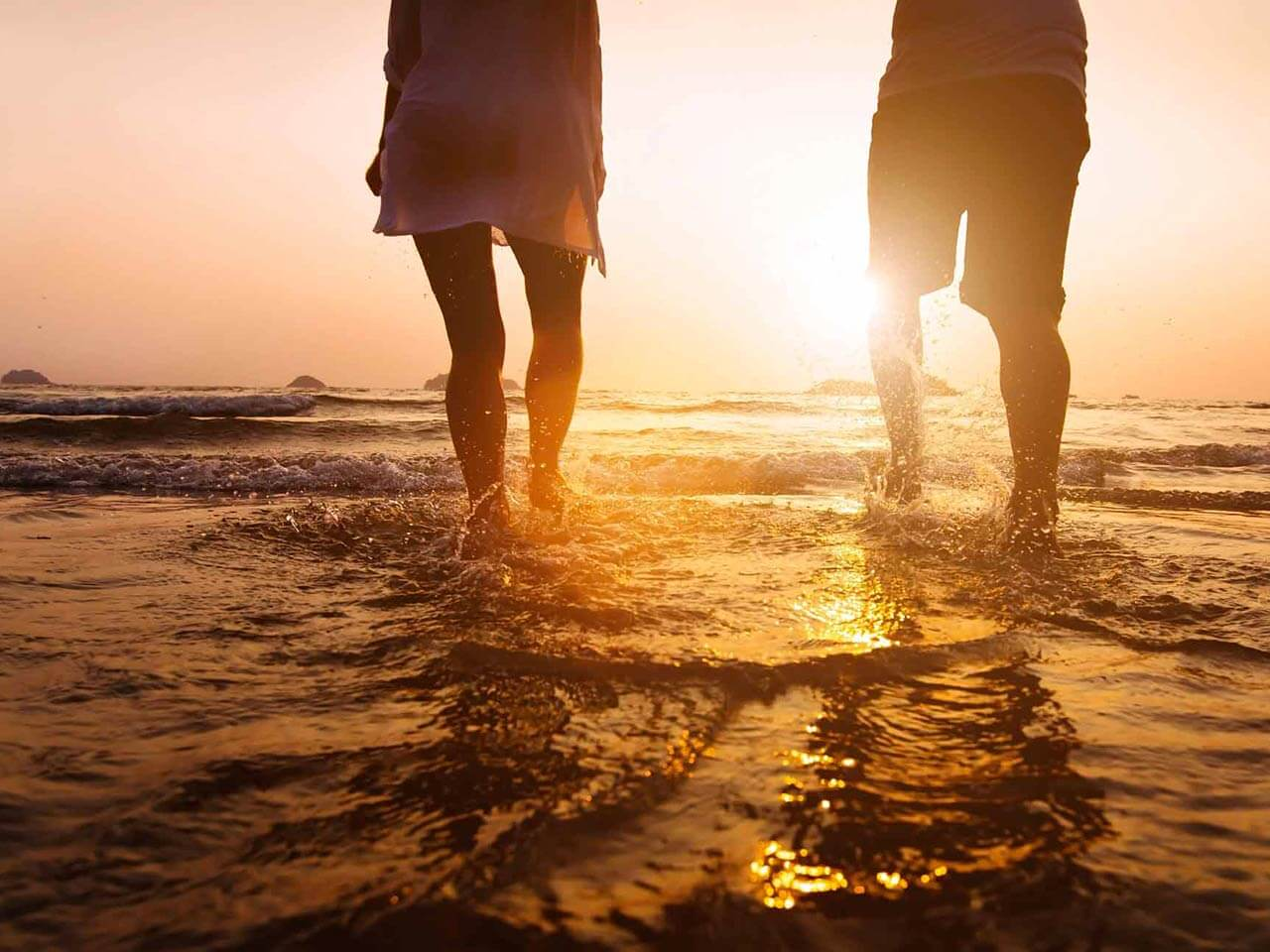 couple wading in beach