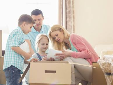 family packing a moving box