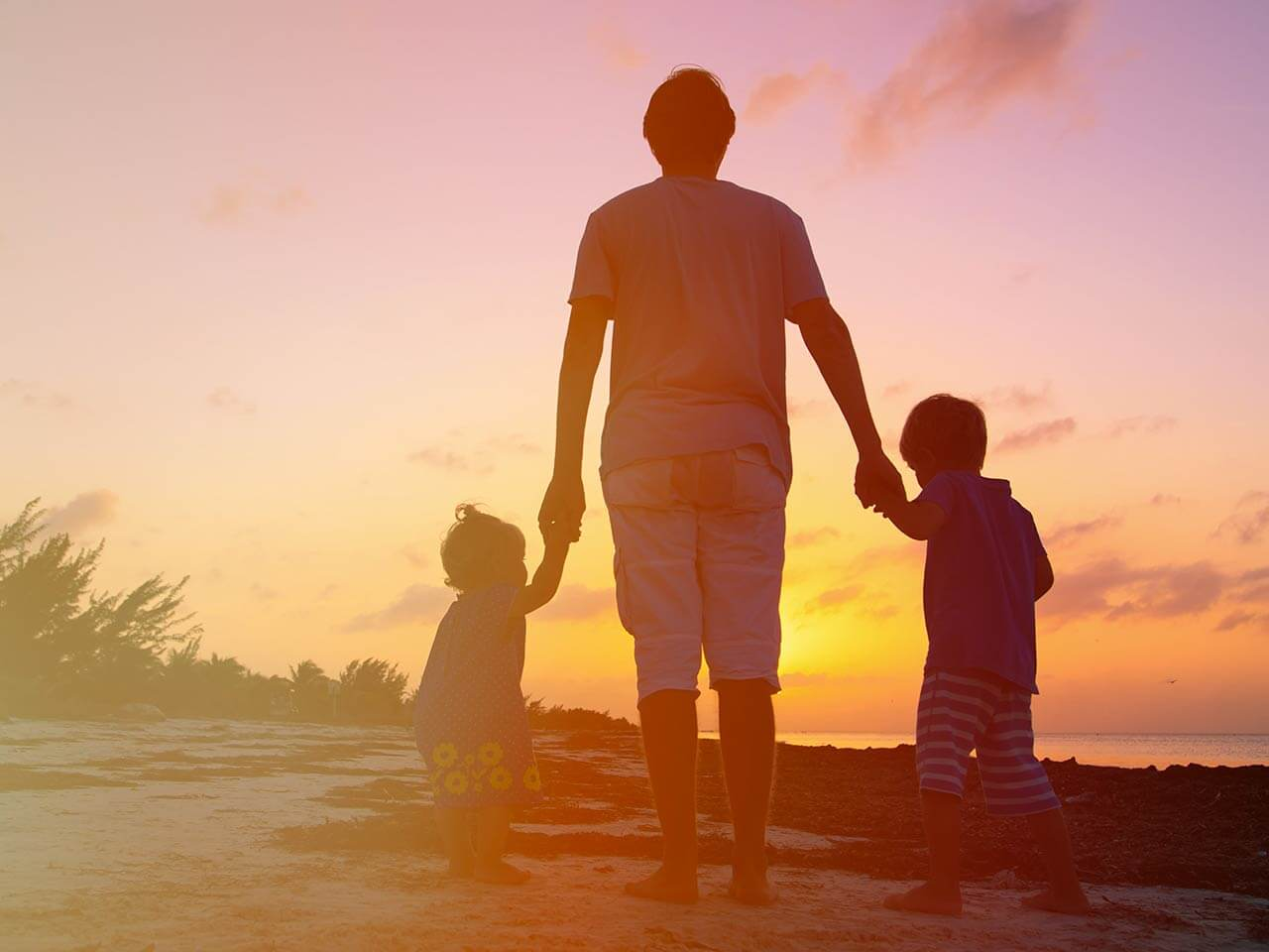 father with kids at the beach