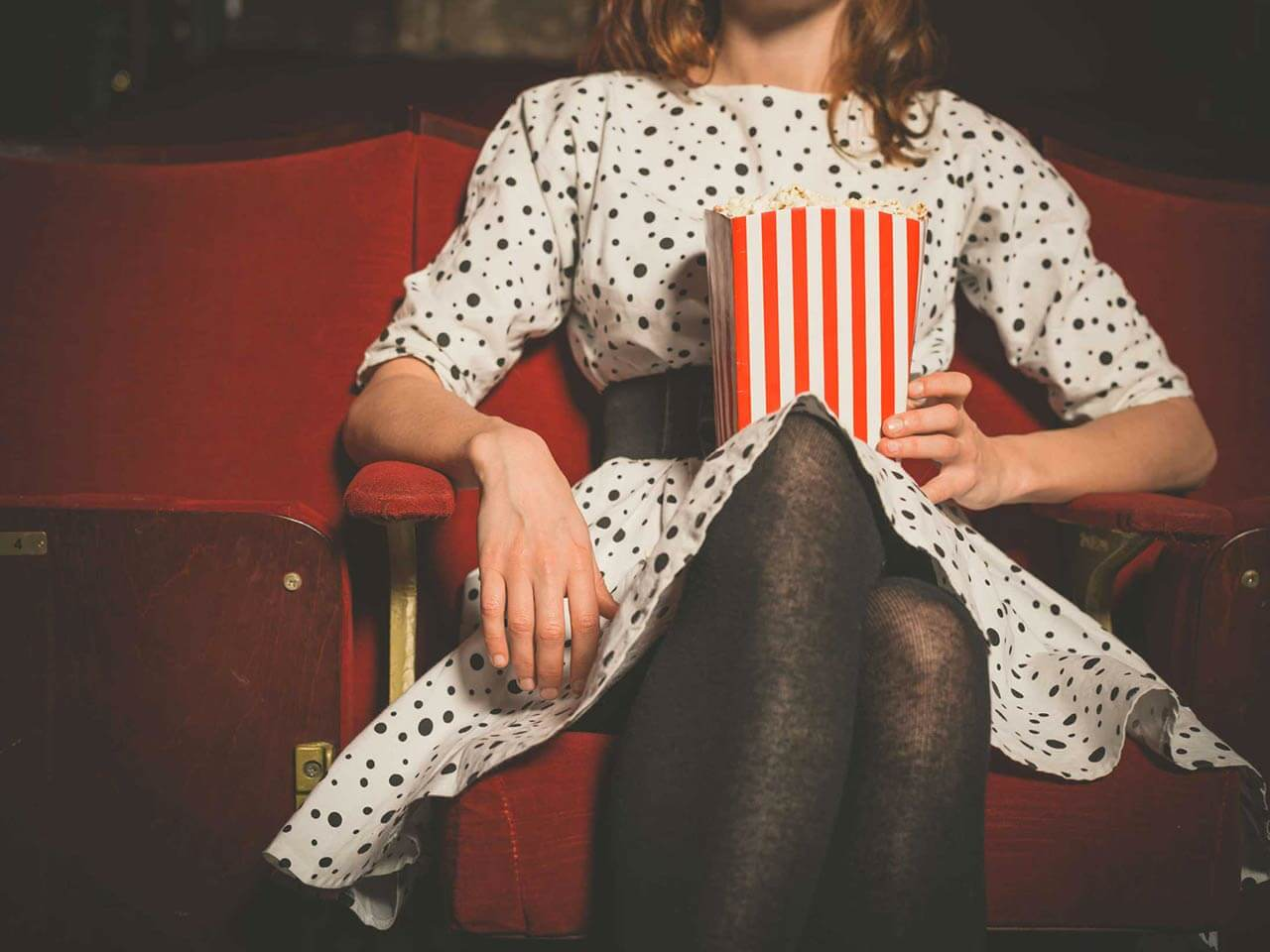 Woman sitting in cinema with popcorn