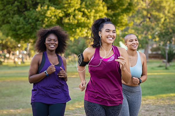 Three women running in park