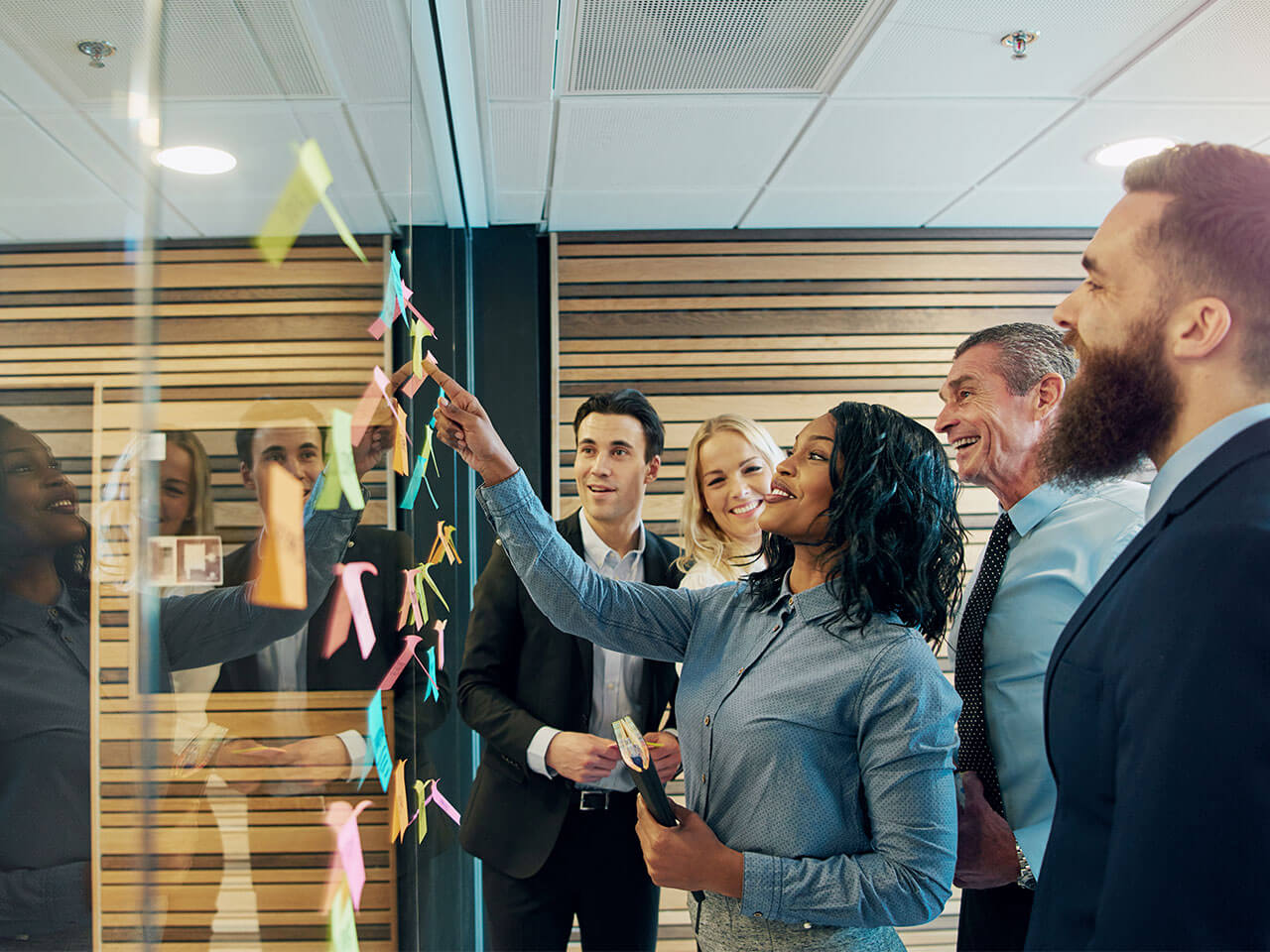 Colleagues putting sticky notes on glass wall