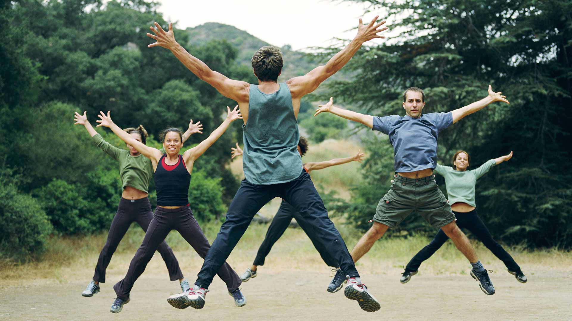 Group doing star jumps in park
