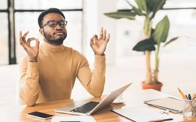 Man meditating at his desk