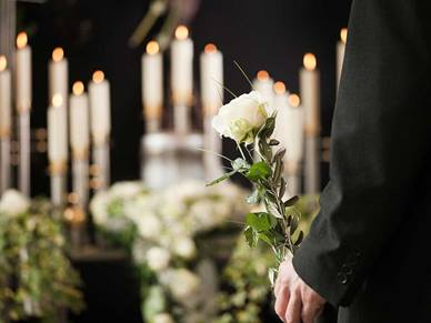 Man standing by candles and flowers