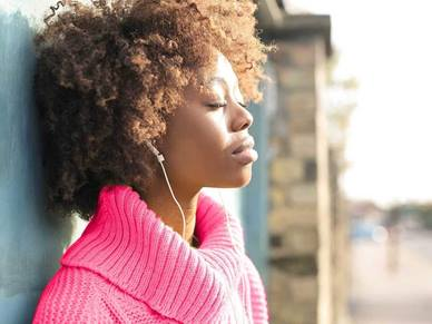 Woman listening to music whilst standing against a wall
