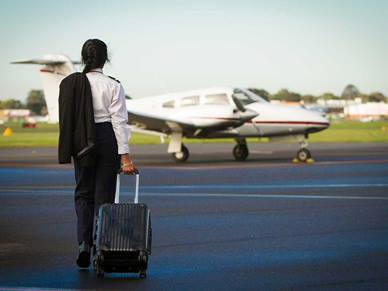 A pilot carrying a suitcase is walking towards a plane