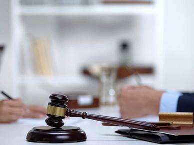 A gavel rests on the table whilst two people are sat opposite each other talking