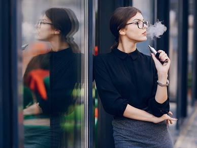 Woman smoking a vape whilst standing against a glass window