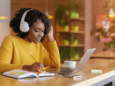 Woman listening to music whilst writing in a notebook