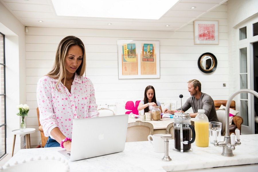 Woman on laptop at home with husband and daughter