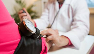 GP taking patients blood pressure