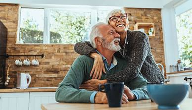 Elderly couple hugging each other in the kitchen