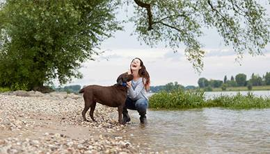 Women hugging dog by a river