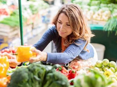 women choosing vegetables at supermarket