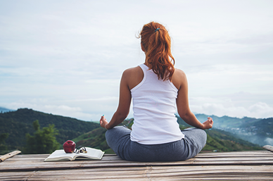 Woman meditating overlooking hills