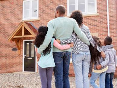 Decorate image of a family standing outside their new home