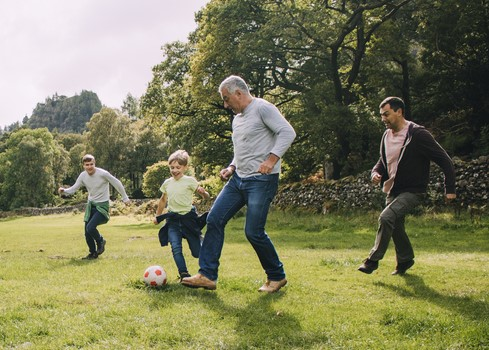 father playing football with family